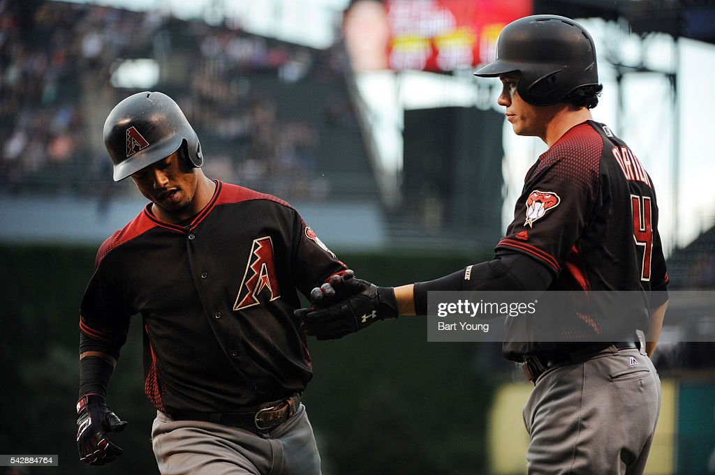 Jean Segura #2 of the Arizona Diamondbacks scores a run in the first inning and is congratulated by teammate Peter O'Brien against the Colorado Rockies at Coors Field on June 24, 2016 in Denver, Colorado.
