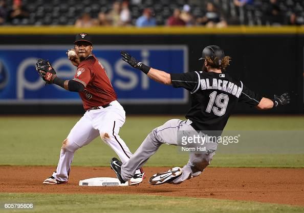 Jean Segura of the Arizona Diamondbacks turns a double play as Charlie Blackmon of the Colorado Rockies slides into second base during the fifth...
