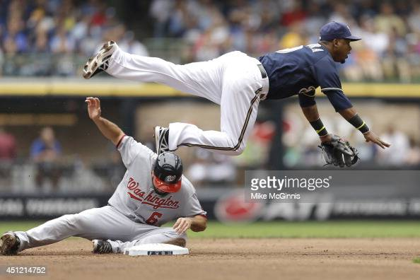Jean Segura of the Milwaukee Brewers attempts the double play as Anthony Rendon of the Washington Nationals slides into second base during the top of...