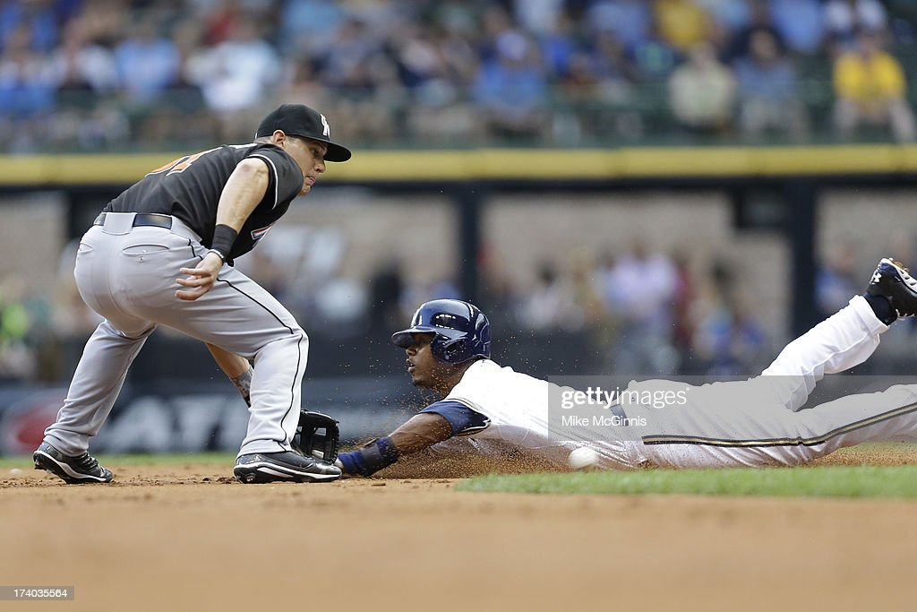 Jean Segura of the Milwaukee Brewers beats the throw to Derek Dietrich of the Miami Marlins in the bottom of the first inning at Miller Park on July...