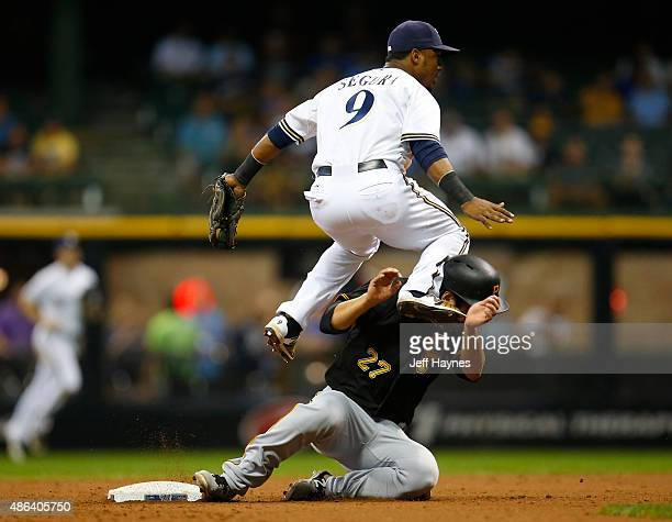 Jean Segura of the Milwaukee Brewers collides with Jung Ho Kang of the Pittsburgh Pirates while turning a double play in the seventh inning at Miller...