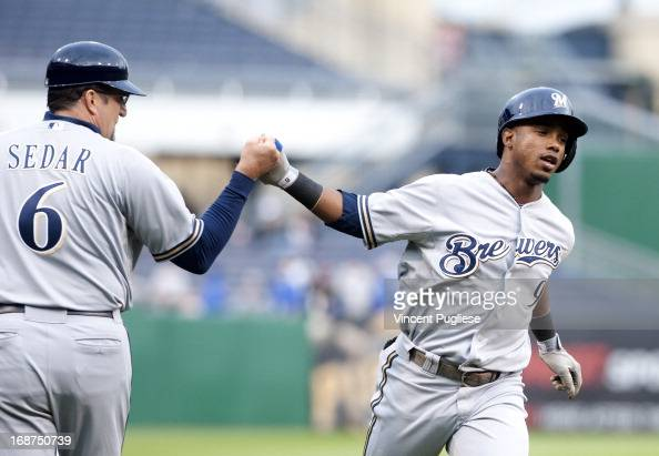 Jean Segura of the Milwaukee Brewers is congratulated by third base coach Ed Sedar after hitting a home run in the first inning against the...