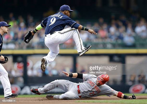 Jean Segura of the Milwaukee Brewers jumps over Skip Schumaker of the Cincinnati Reds while turning a double play in the top of the first inning at...