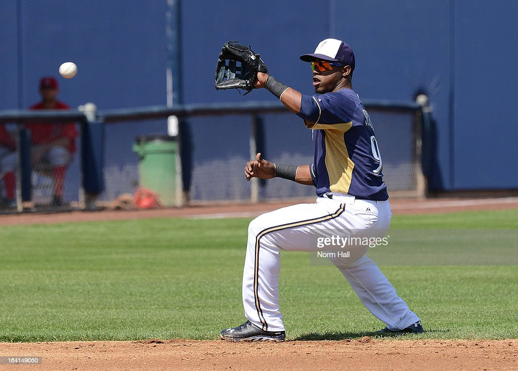 Jean Segura #9 of the Milwaukee Brewers makes a play on a bouncing ball against the Los Angeles Angels at Maryvale Baseball Park on March 19, 2013 in Maryvale, Arizona.