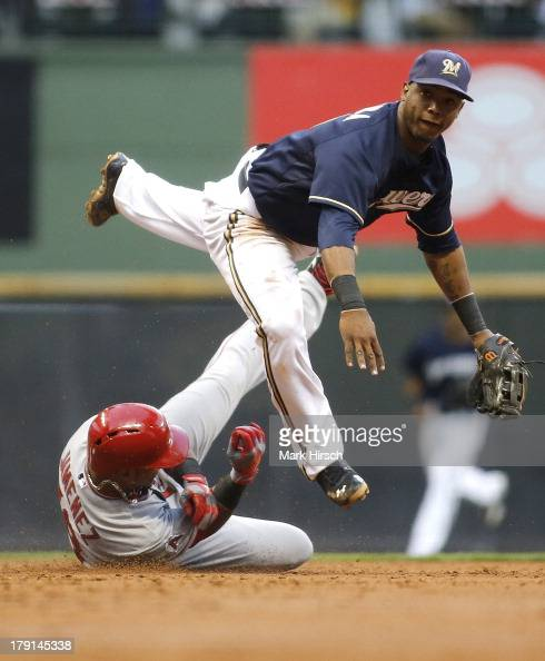 Jean Segura of the Milwaukee Brewers makes the double play over Luis Jimenez of the Los Angeles Angels of Anaheim at second base during third inning...