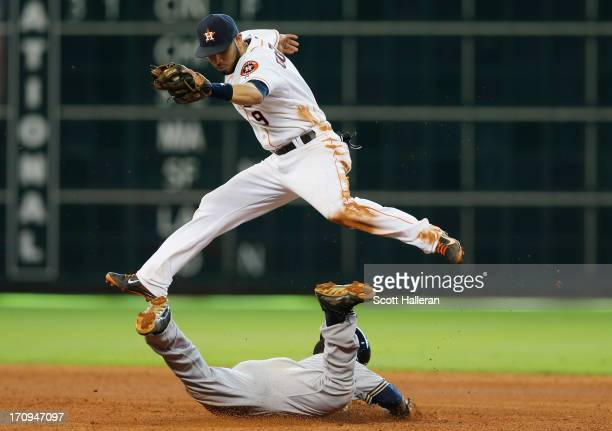 Jean Segura of the Milwaukee Brewers slides safely into second base in the seventh inning under the tag of Marwin Gonzalez of the Houston Astros at...