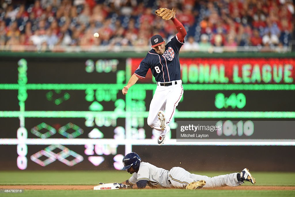 Jean Segura #9 of the Milwaukee Brewers steals second base under Danny Espinosa #8 of the Washington Nationals in the third inning during a baseball game at Nationals Park on August 21, 2015 in Washington, DC.