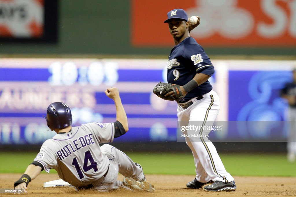 Jean Segura #9 of the Milwaukee Brewers turns the double play as Josh Rutledge #14 slides late into second base in the top of the second inning against the Colorado Rockies at Miller Park on April 3, 2013 in Milwaukee, Wisconsin.