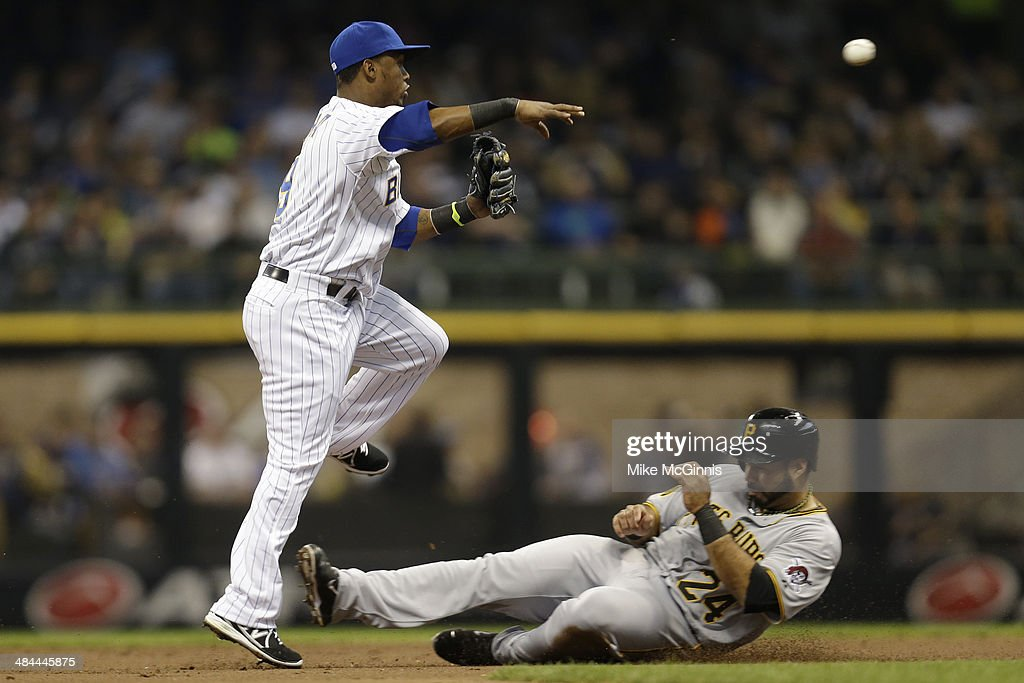 Jean Segura #9 of the Milwaukee Brewers turns the double play as Pedro Alvarez #24 of the Pittsburgh Pirates slides into second base during the top of the second inning at Miller Park on April 12, 2014 in Milwaukee, Wisconsin.