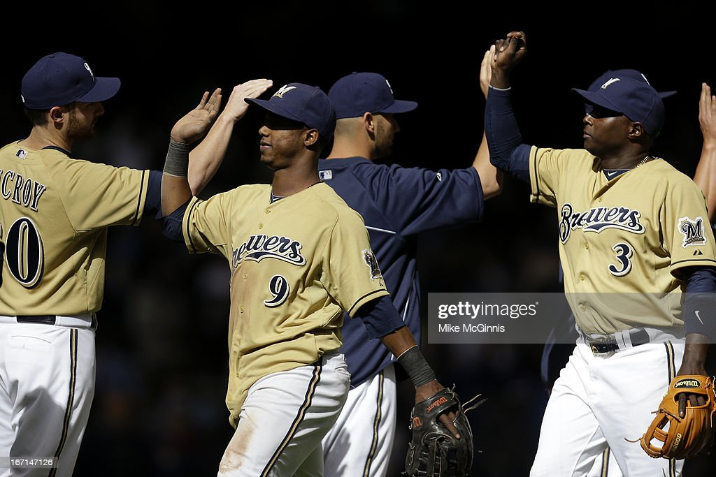 Jean Segura #9 of the Milwaukee Brewers Yuniesky Betancourt and Jonathan Lucroy #20 celebrate after the 4-2 win and sweeping the Chicago Cubs in the three game series at Miller Park on April 21, 2013 in Milwaukee, Wisconsin.