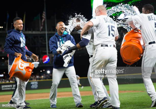 Jean Segura of the Seattle Mariners center gets an ice bath from Kyle Seager and Guillermo Heredia right on the field after scoring the winning run...