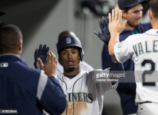 Jean Segura of the Seattle Mariners is congratulated by teammates in the dugout after scoring on a hit by Ben Gamel of the Seattle Mariners off of...