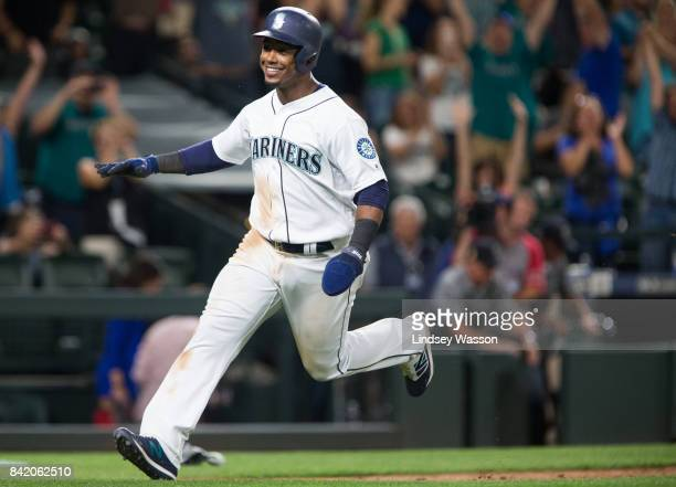 Jean Segura of the Seattle Mariners smiles as he scores the winning run on a wild pitch by Blake Treinen of the Oakland Athletics in the ninth inning...