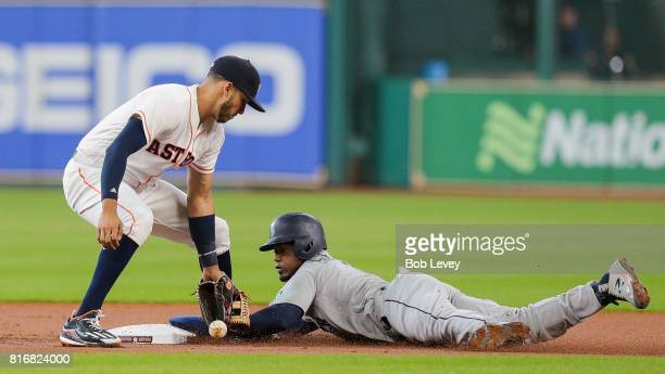 Jean Segura of the Seattle Mariners steals second base in the first inning ahead of the throw to Carlos Correa of the Houston Astros who was unable...