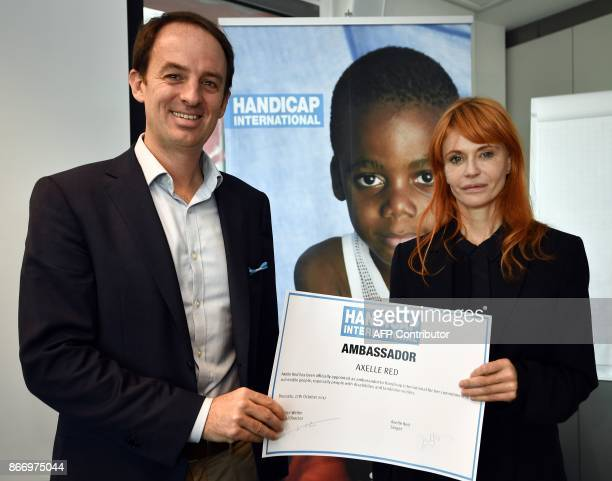 Jean Van Wetter of Handicap International Belgium and Belgian singer Axelle Red pose during a press conference as Axelle Red is officially appointed...