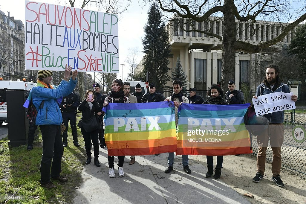 Jean-Baptiste Redde (L), aka Voltuan, holds a sign reading 'Let's save Aleppo, stop the bombs' as he takes part with others in a demonstration in front of the Russian Embassy in Paris on February 10, 2016 to demand a stop to the bombardment of Aleppo and an alternative peace plan for the conflict in Syria. / AFP / MIGUEL MEDINA