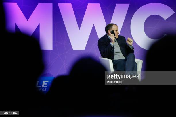 JeanBriac Perrette chief executive officer of Discovery Communications Inc holds out his mobile phone while speaking on the third day of Mobile World...