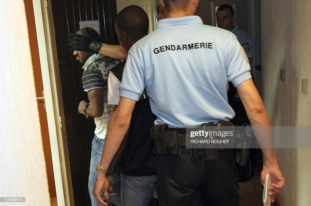 Jean-Charles A. (L), suspected of murdering a 4 year-old child in Saint-Benoit, on the French island of Reunion, is led by police officers during his appearance before the Prosecutor of the High Court of Saint Denis on June 20, 2013. The 37 year-old man is suspected of killing and beheading the child on the morning of June 19, acting in revenge after his ex-girlfriend told him he was not the child's father, the prosecutor of Saint-Denis announced on June 20. The body of a four year old child, Matteo, was discovered decapitated and partially burned, early on the morning of June 19, 2013 in a house in Saint-Benoit.