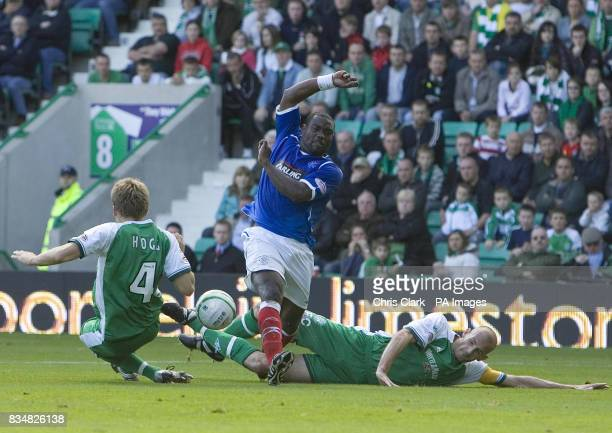 JeanClaude Darcheville of Rangers is tackled by Hibernian defender Chris Hogg and Hibernian captain Rob Jones during the Clydesdale Bank Scottish...