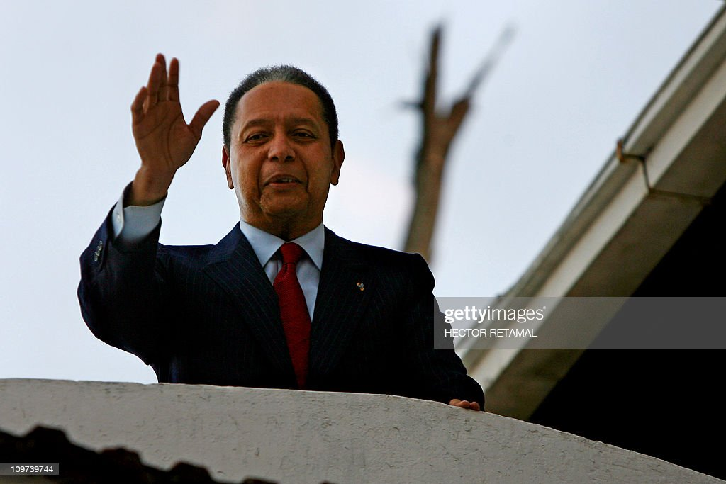 <a gi-track='captionPersonalityLinkClicked' href=/galleries/search?phrase=Jean-Claude+Duvalier&family=editorial&specificpeople=2596261 ng-click='$event.stopPropagation()'>Jean-Claude Duvalier</a> greets supporters after giving a press conference at the house that these days are staying in Petion Ville, Port au Prince. Hector Retamal January 21, 2011. The mystery of <a gi-track='captionPersonalityLinkClicked' href=/galleries/search?phrase=Jean-Claude+Duvalier&family=editorial&specificpeople=2596261 ng-click='$event.stopPropagation()'>Jean-Claude Duvalier</a>'s return to Haiti, out of the blue and in a moment of national chaos and instability, may be explained not by a thirst for power but another gnawing human need: money. The former dictator said January 21, 2011 that he flew home after nearly 25 years in exile 'to show my solidarity at this difficult moment,' and he expressed 'deep sorrow' for those who say they were victims of his regime. But human rights activists and experts believe it may have been a maneuver to prevent the confiscation of at least $5.7 million in frozen Swiss bank accounts. AFP PHOTO / HECTOR RETAMAL