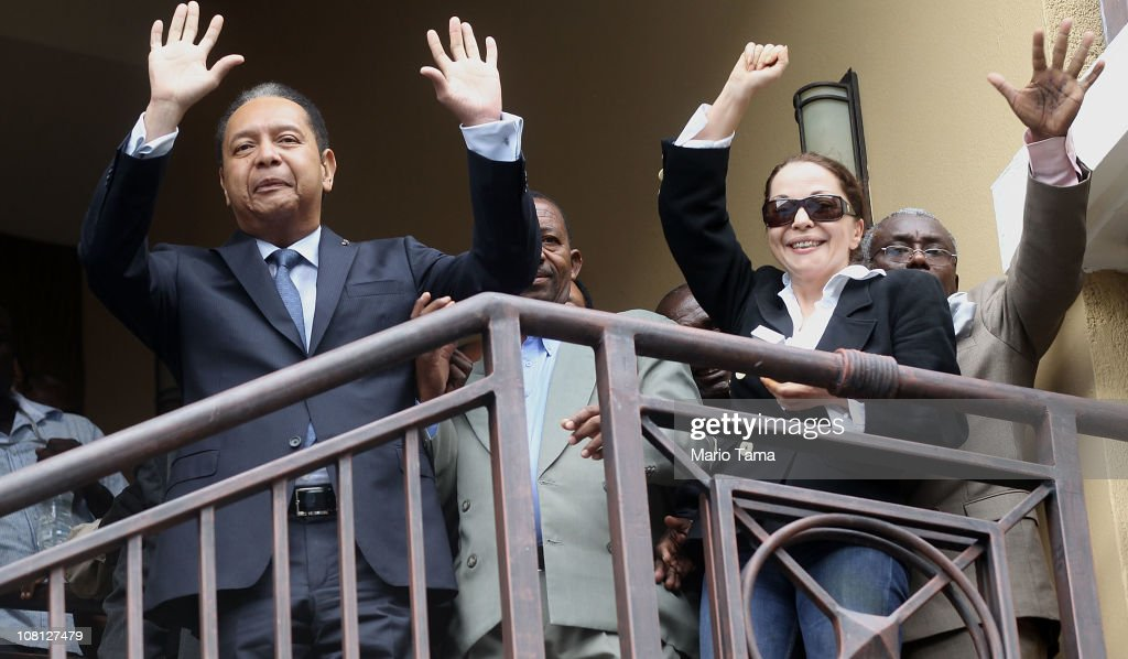 <a gi-track='captionPersonalityLinkClicked' href=/galleries/search?phrase=Jean-Claude+Duvalier&family=editorial&specificpeople=2596261 ng-click='$event.stopPropagation()'>Jean-Claude Duvalier</a> (L), the former Haitian leader known as 'Baby Doc', waves as he is taken into custody by Haitian police with his girlfriend Veronique Roy (R) at the Hotel Karibe on January 18, 2011 in Port-au-Prince, Haiti. Duvalier was initially greeted by supporters upon returning to his homeland for the first time in 25 years from his exile in France. Duvalier was taken to a downtown courthouse and Haitian authorities presumably questioned Duvalier to determine whether he should be prosecuted for stealing from the treasury during his rule and for crimes against humanity.