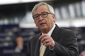 JeanClaude Juncker President of the European Commission speaks as members of the right wing section of the parliament hold placards agains the TTIP...