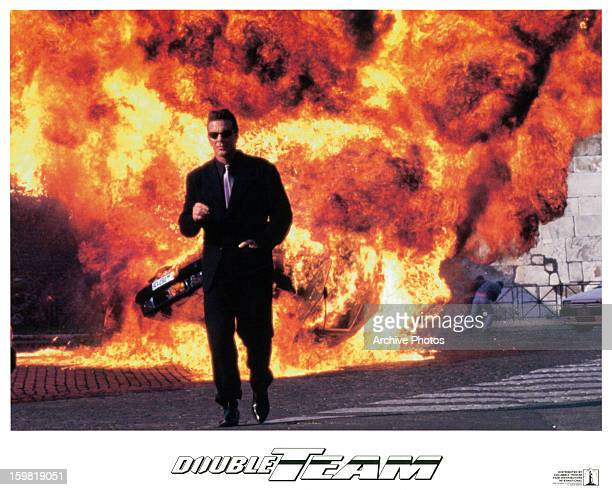 JeanClaude Van Damme walks away from an explosion in a scene from the film 'Double Team' 1997