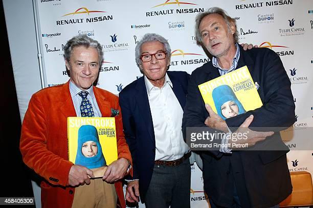 JeanDaniel Lorieux standing between Book publishers Pierre Gradenigo and Alain de Gourcuff attend JeanDaniel Lorieux signs his Book 'Sunstroke' at...