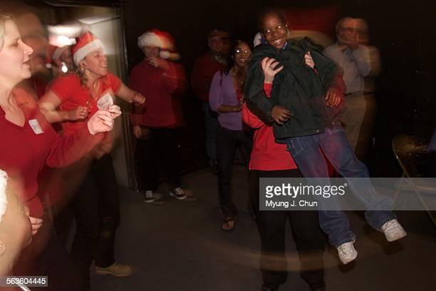Jeanesha Norwood gets a lift and spin while dancing to Christmas tunes with members of the LA Connection Comedy Theatre in Sherman Oaks during...