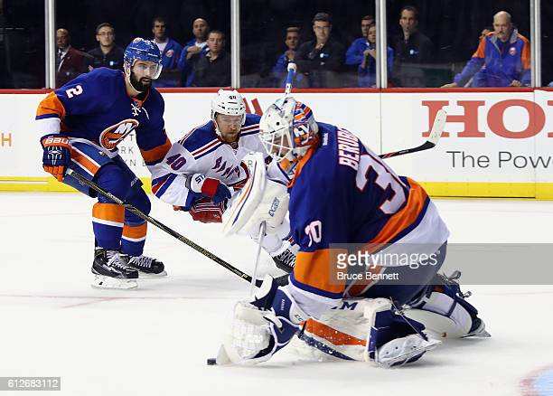 JeanFrancois Berube of the New York Islanders brushes aside a shot by Michael Grabner of the New York Rangers during the third period at the Barclays...