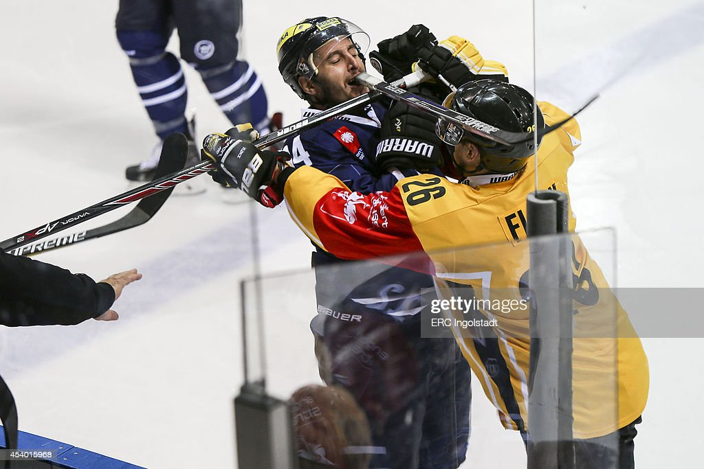 Jean-Francois Boucher (#84 ERC Ingolstadt) is checked into the boards by Flinck Markku #26 yellow SAI - Game 2 of 6 during the Champions Hockey League group stage game between ERC Ingolstadt and SaiPa Lappeenranta on August 23, 2014 in Ingolstadt, Germany.
