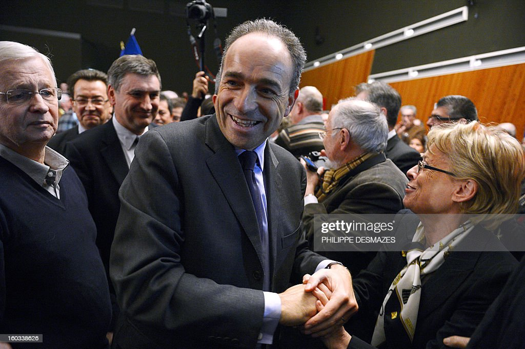 Jean-Francois Cope, the head of France's right-wing UMP opposition, shakes hands as he arrives to give a speech during a meeting with militants on January 29, 2013 in Villeurbanne near Lyon.