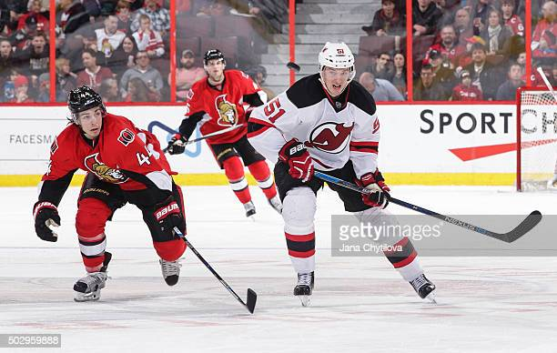 JeanGabriel Pageau of the Ottawa Senators and Sergey Kalinin of the New Jersey Devils race for the airborne puck at Canadian Tire Centre on December...