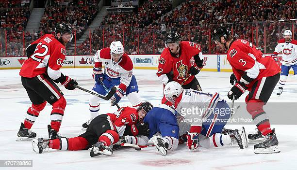 JeanGabriel Pageau of the Ottawa Senators lies on the ice after a faceoff against the Montreal Canadiens as Eric GrybaErik Condra and Marc Methot go...