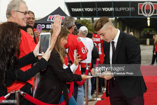 JeanGabriel Pageau of the Ottawa Senators signs an autograph on the red carpet prior to the start of a game against the Detroit Red Wings at Canadian...