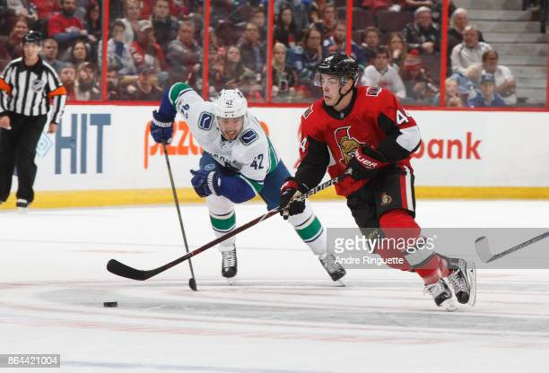 JeanGabriel Pageau of the Ottawa Senators skates against Alexander Burmistrov of the Vancouver Canucks at Canadian Tire Centre on October 17 2017 in...