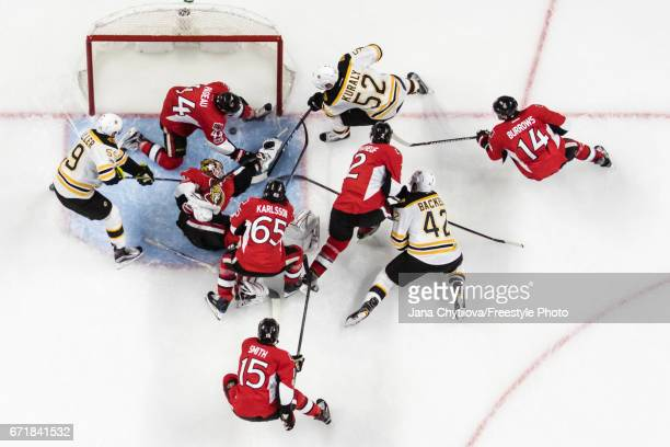 JeanGabriel Pageau of the Ottawa Senators stops the puck crossing in the net as Sean Kuraly David Backes and Tim Schaller of the Boston Bruins buzz...