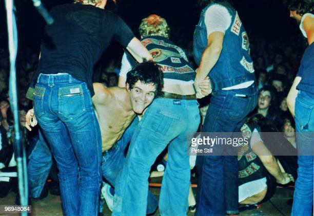 JeanJacques Burnel is dragged back on stage by Hells Angels during The Stranglers concert at Bracknell Sports Centre on September 17th 1977 in...
