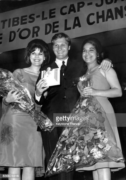 JeanJacques Debout remporte le 1er concours de la chanson française et montre son trophée une 'Rose d'or' entouré des chanteuses Isa Bardot et Frida...
