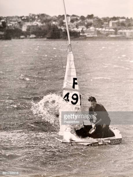 JeanJacques Herbulot of France attempts to bail out his boat before capsizing in the Firefly class sailing event due to strong winds and heavy seas...