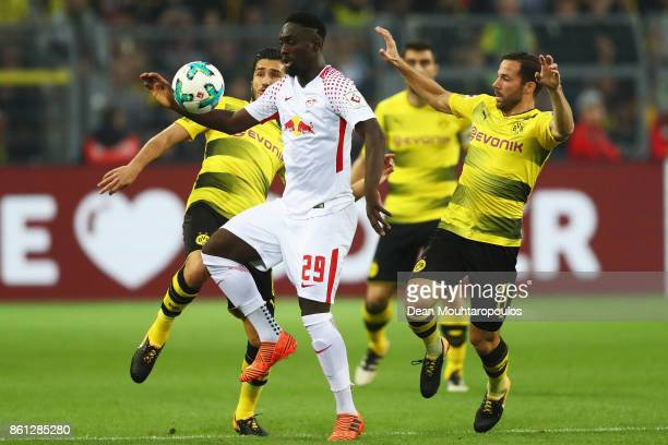 JeanKevin Augustin of RB Leipzig battles for the ball with Nuri Sahin and Gonzalo Castro of Borussia Dortmund during the Bundesliga match between...