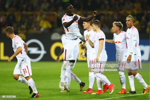 JeanKevin Augustin of RB Leipzig celebrates scoring his teams third goal of the game with team mates during the Bundesliga match between Borussia...