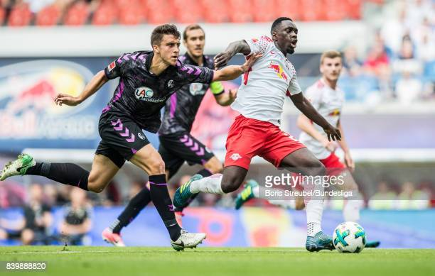 JeanKevin Augustin of RB Leipzig is challenged by MarcOliver Kempf of SC Freiburg during the Bundesliga match between RB Leipzig and SportClub...