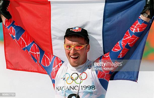 JeanLuc Cretier of France holds the French flag after winning the men's Olympic downhill 13 February in Hakuba Cretier won the race with a time of...