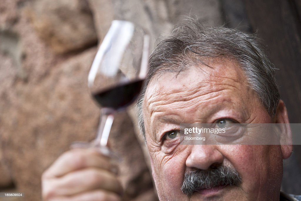 Jean-Luc Matha, a winemaker and owner of the Jean-Luc Matha vineyard, checks a glass of his red wine for the color while at his vineyard in Clairvaux, France, on Thursday, Oct. 24, 2013. France's stocks of wine fell to the lowest in at least 12 years after the country's production plunged 19 percent last year, crop office FranceAgriMer said. Photographer: Balint Porneczi/Bloomberg via Getty Images