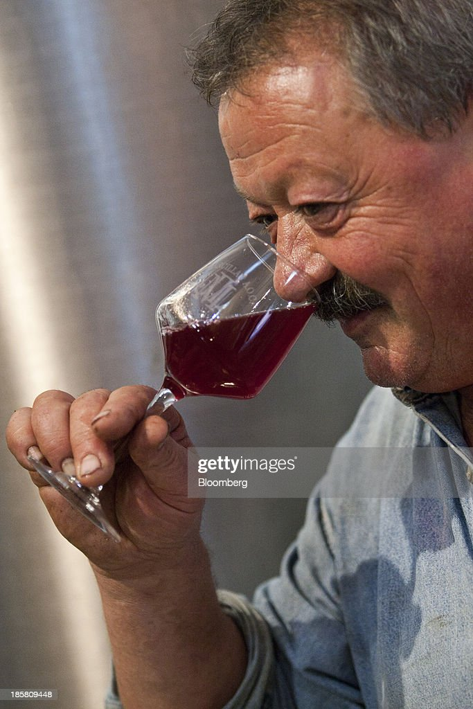Jean-Luc Matha, a winemaker and owner of the Jean-Luc Matha vineyard, smells the bouquet on a glass of red wine from his vineyard in Clairvaux, France, on Thursday, Oct. 24, 2013. France's stocks of wine fell to the lowest in at least 12 years after the country's production plunged 19 percent last year, crop office FranceAgriMer said. Photographer: Balint Porneczi/Bloomberg via Getty Images