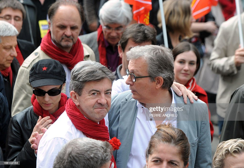 Jean-Luc Melenchon (2nd L), leader of Front de Gauche (Left Front) left wing party, looks on hugging French Communist Party (PCF) national secretary Pierre Laurent (R) as they take part in a demonstration at Melenchon's call on May 5, 2013 in Paris, called by , to protest 'against the austerity, against the finance and to ask for a Sixth Republic'. When France's president Francois Hollande swept to power on May 2012 on a wave of discontent, he could hardly have imagined that a year later he would be the most unpopular president in modern French history. AFP PHOTO / PIERRE ANDRIEU