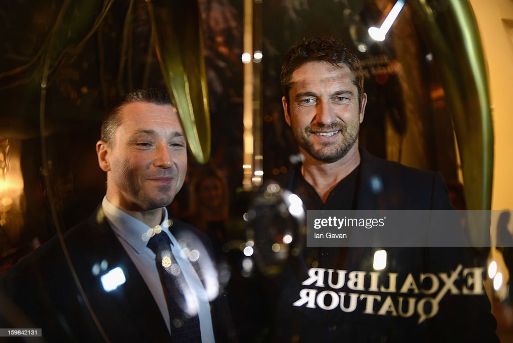 Jean-Marc Pontroue (L), CEO of Roger Dubuis looks at the Excalibur Quatuor watch with actor and friend of the brand <a gi-track='captionPersonalityLinkClicked' href=/galleries/search?phrase=Gerard+Butler+-+Actor&family=editorial&specificpeople=202258 ng-click='$event.stopPropagation()'>Gerard Butler</a> as he visits the Roger Dubuis booth during the 23rd Salon International de la Haute Horlogerie at the Geneva Palexpo on January 21, 2013 in Geneva, Switzerland.