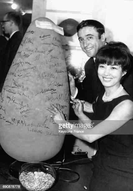 JeanMarc Thibault et May WouKi l'épouse du peintre Zao WouKi signant une dragée géante à l'occasion de l'inauguration d'une 'boutique culturelle'...