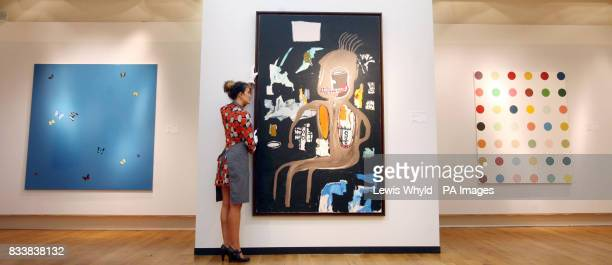 JeanMichel Basquiat's The Thinker is adjusted at Christie's in London by a worker The work is expected to fetch 2000 2000 at auction Works by Damien...